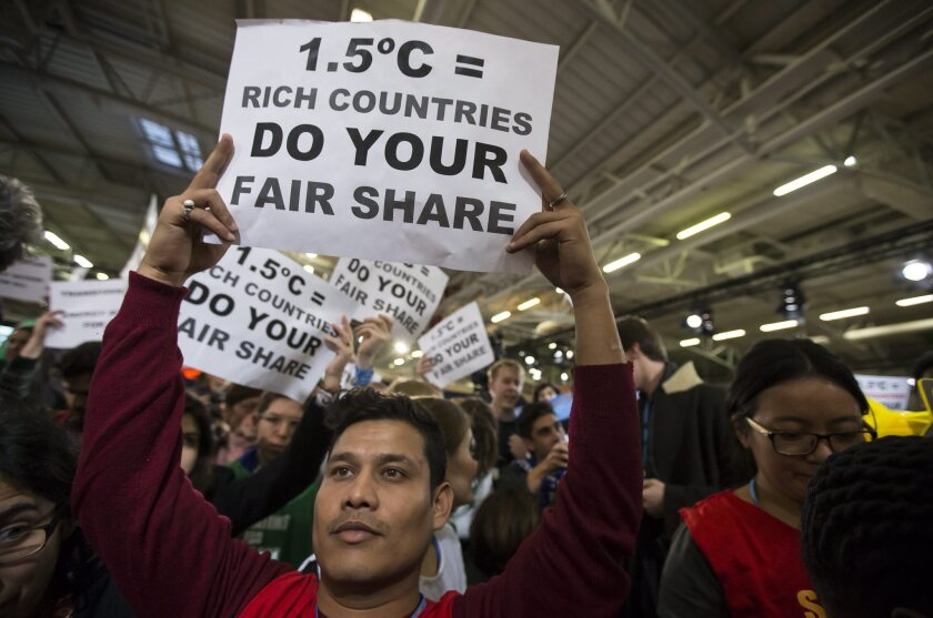 Activists stage a sit-in Dec. 9 urging countries to adopt ambitious goals at the U.N. climate conference in Le Bourget, north of Paris.