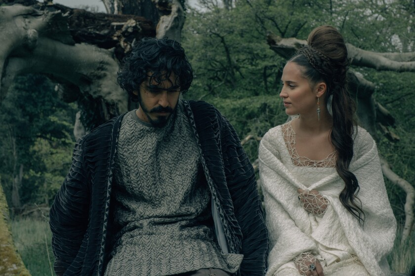 """Dev Patel and Alicia Vikander sit next to each other in """"The Green Knight."""""""