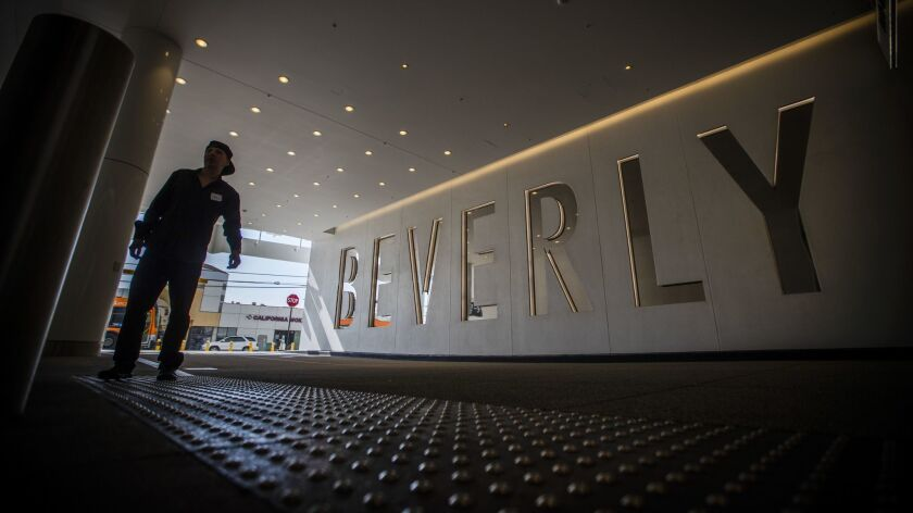 A man walks in near a large sign at the valet entrance to The Beverly Center.