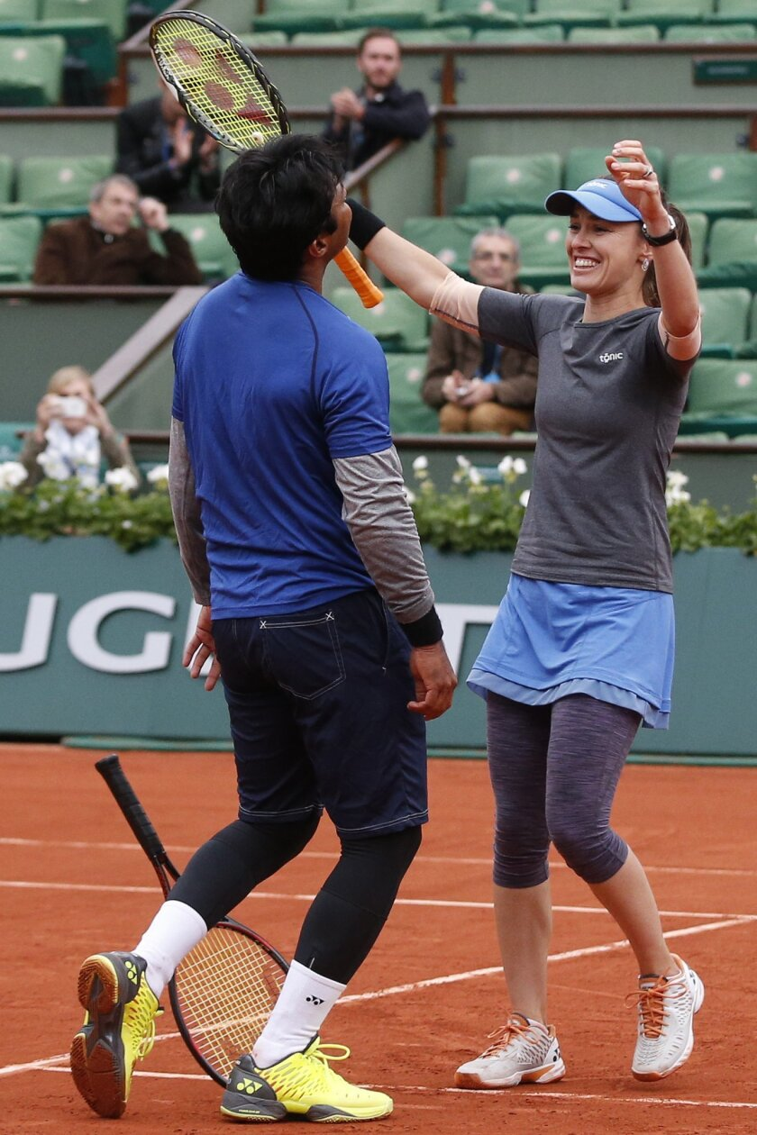 Switzerland's Martina Hingis, right, and India's Leander Paes celebrate winning the mixed doubles final of the French Open tennis tournament against India's Sania Mirza and Croatia's Ivan Dodic at the Roland Garros stadium in Paris, France, Friday, June 3, 2016. (AP Photo/Alastair Grant)