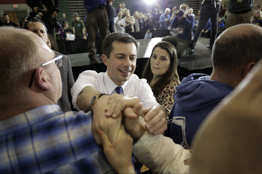 Democratic presidential candidate former South Bend, Ind., Mayor Pete Buttigieg, center, greets people in the audience at the conclusion of a campaign rally, Sunday, Feb. 9, 2020, in Dover, N.H. (AP Photo/Steven Senne)