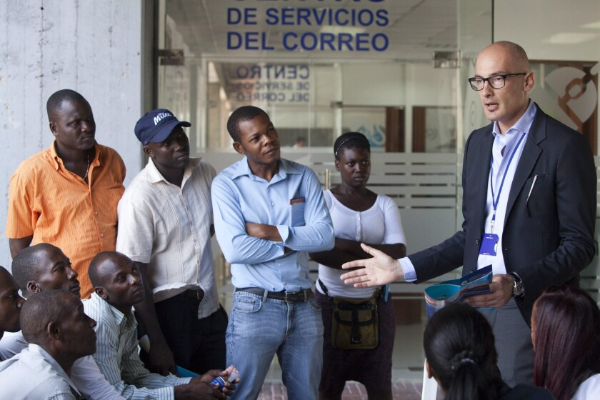 An official with the International Organization for Migration talks to people of Haitian origin at the headquarters of the Ministry of Interior in Santo Domingo, Dominican Republic, on June 2.