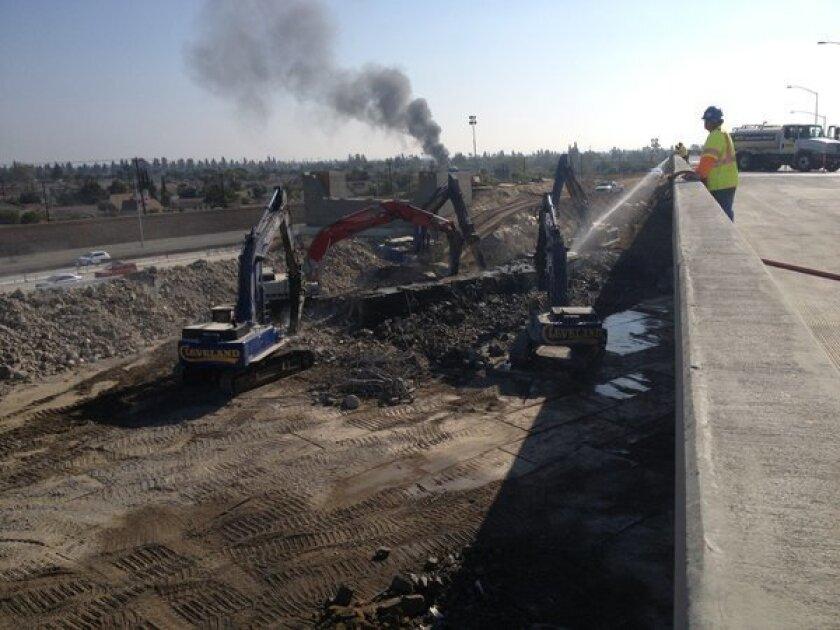 Demolition crews work on bridge removal project on 405 Freeway in Orange County.