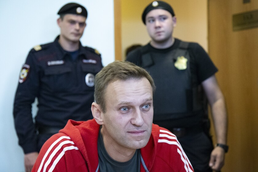 FILE- In this file photo taken on Thursday, Aug. 22, 2019, Russian opposition leader Alexei Navalny speaks to the media prior to a court session in Moscow, Russia. The German government on Friday criticized an announcement by Russia's foreign minister that Moscow has imposed sanctions against German and French officials in response to EU measures taken over the poisoning of Russian opposition leader Alexei Navalny. (AP Photo/Alexander Zemlianichenko, File)