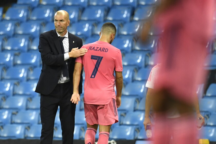 Real Madrid's head coach Zinedine Zidane pats Real Madrid's Eden Hazard as he leaves the pitch during the Champions League, round of 16, second leg soccer match between Manchester City and Real Madrid at the Etihad Stadium in Manchester, England, Friday, Aug. 7, 2020. (Peter Powell/Pool Photo via AP)