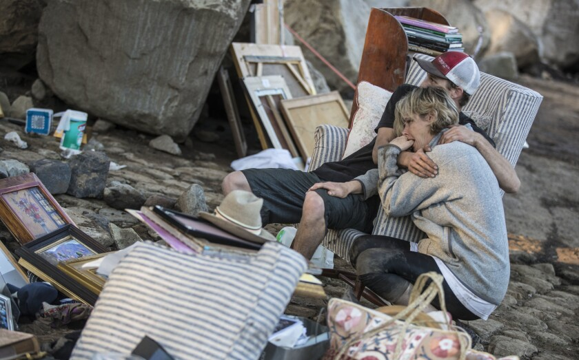 Travis Zehntner comforts Teresa Drenick on Thursday amid the belongings of her sister Rebecca Riskin, who was killed in the mudslide. Family and friends salvaged family photos and furnishings left in the home on Glen Oaks Drive.
