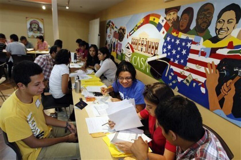 Immigrant Angel Eduardo Aguiluz, left, from Honduras, get help with documents and filling for the Deferred Action for Childhood Arrivals program at Casa de Maryland in Langley Park, Md., on Aug. 15,  2012. (AP Photo/Jose Luis Magana)