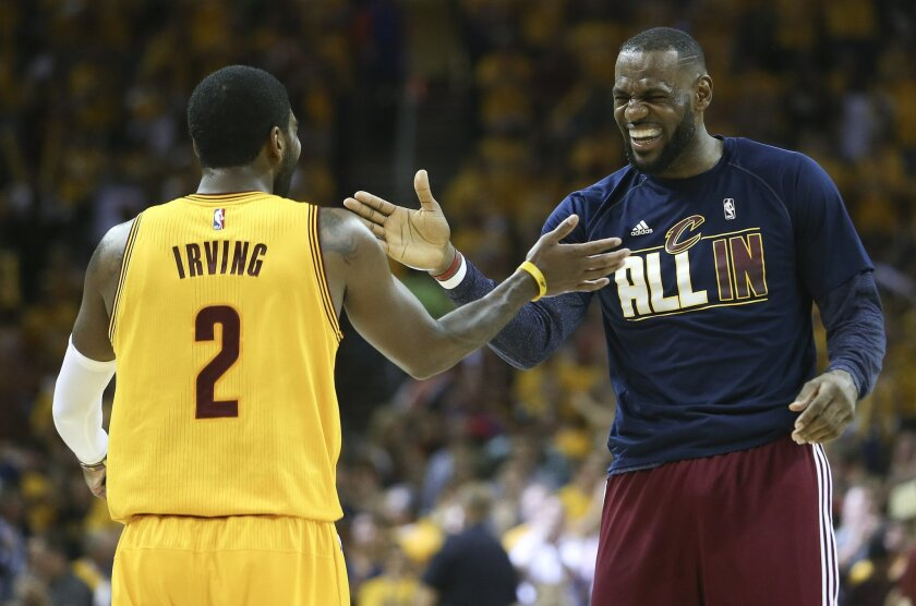 FILE - In this Tuesday, May 266, 2015, file photo, Cleveland Cavaliers forward LeBron James and guard Kyrie Irving (2) slap hands during a timeout in the first half of Game 4 of the NBA basketball Eastern Conference Finals against the Atlanta Hawks in Cleveland. While the Golden State Warriors are making their first appearance in 40 years, this is nothing new for James, in the finals for the fifth straight year. (AP Photo/Ron Schwane, File)