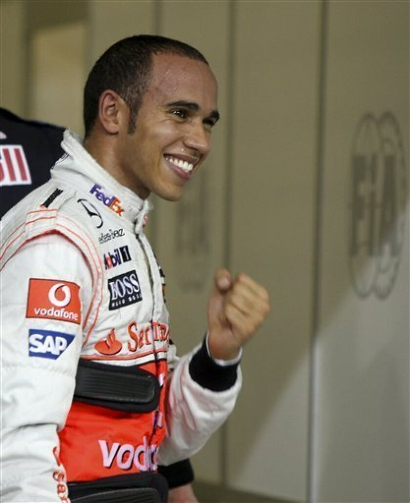 McLaren Mercedes driver Lewis Hamilton of Britain reacts after setting pole position for Sunday's Abu Dhabi Grand Prix at the Yas Marina racetrack, in Abu Dhabi, United Arab Emirates, Saturday, Oct. 31, 2009. The Emirates Formula One Grand Prix will take place on Sunday, Nov.1. (AP Photo/Luca Bruno)