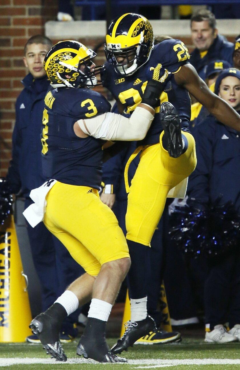 Michigan's Jourdan Lewis, right, celebrates with teammate Desmond Morgan after breaking up a pass to Rutgers' Carlton Agudosi during the second half of an NCAA college football game Saturday, Nov. 7, 2015, in Ann Arbor, Mich. Michigan defeated Rutgers 49-16. (AP Photo/Duane Burleson)