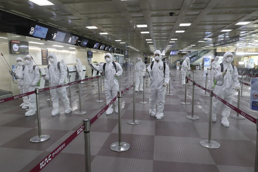 South Korean army soldiers wearing protective suits spray disinfectant to prevent the spread of the new coronavirus at Daegu International Airport.