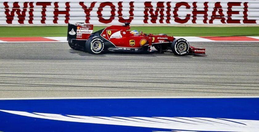 Un coche de la escudería Ferrari pasa frente a un cartel en homenaje a Michael Schumacher. EFE/Archivo