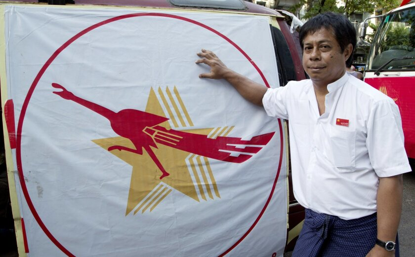 In this Friday, Nov. 6, 2015 photo, Zay Ta, chairman of the New Society Party, stands by his party's symbol, four stars and a peacock in Yangon, Myanmar. Nine of the political parties contesting the country's historic election on Sunday Nov. 8 are using the peacock as their logo, with most bearing