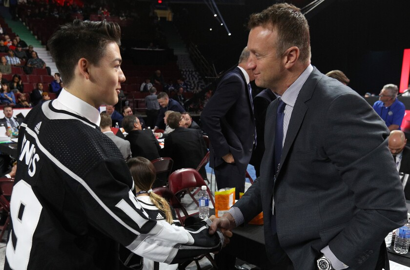 Jordan Spence, left, is greeted by Kings general manger Rob Blake after being selected 95th overall by the Kings in the 2019 NHL draft. Replenishing the Kings' farm system has been one of Blake's top priorities.