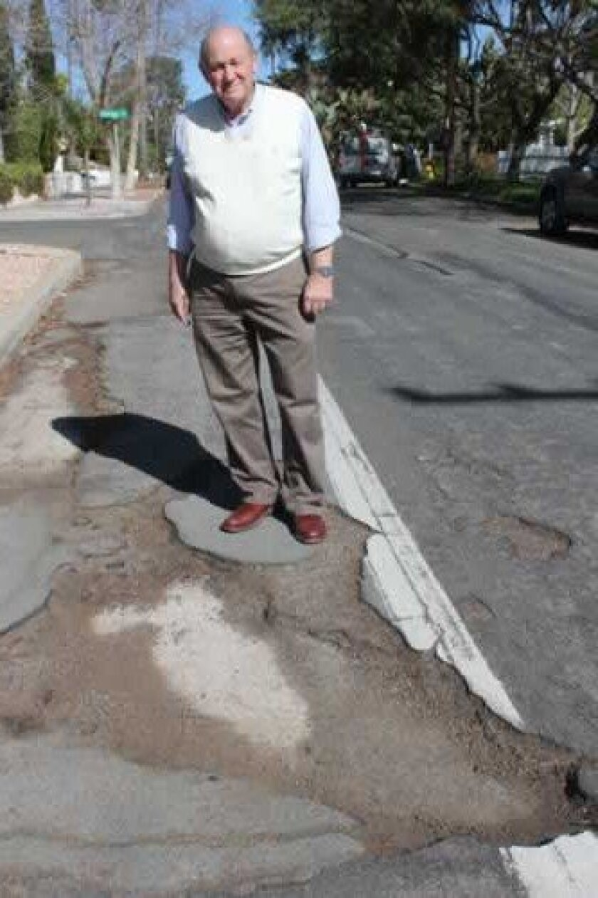 Bird Rock resident Joseph Chalmers stands near one of the many large craters on Forward Street, which were left untouched by city workers when they patched a few potholes there in early march. Pat Sherman