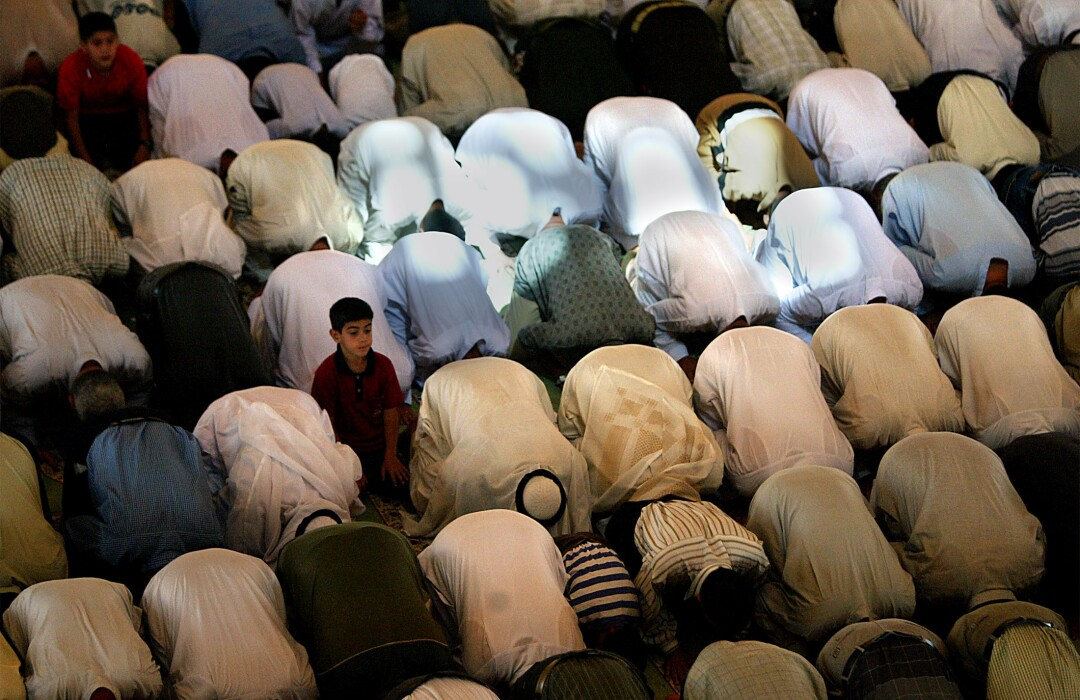 پسری در میان صف افرادی نشسته است که روی نماز روی زمین تعظیم می کنند