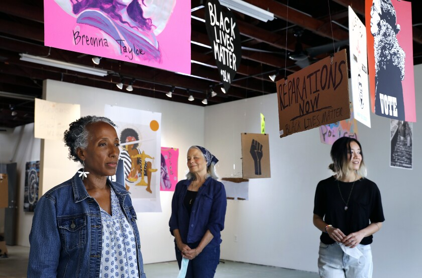 Brenda Thompson, Peggy Sivert and Tatum Hawkins, of SoLA Contemporary stand under protest signs suspended from the ceiling