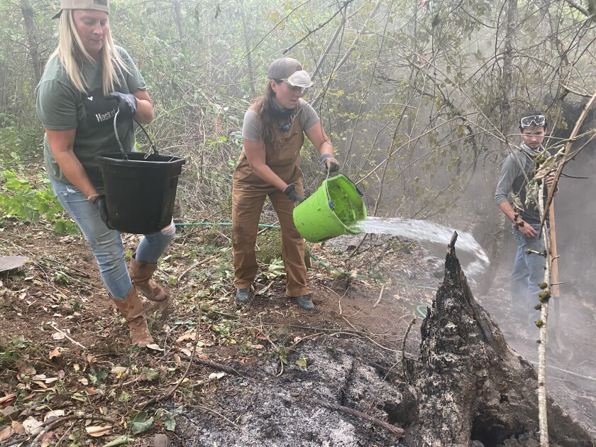 A woman tosses a bucket of water on a smoldering hot spot in the woods