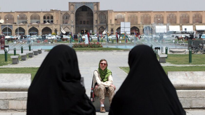 ** FILE- ** Iranian women wear the 'chador', a head-to-toe garment, as they pass a tourist in Isfaha