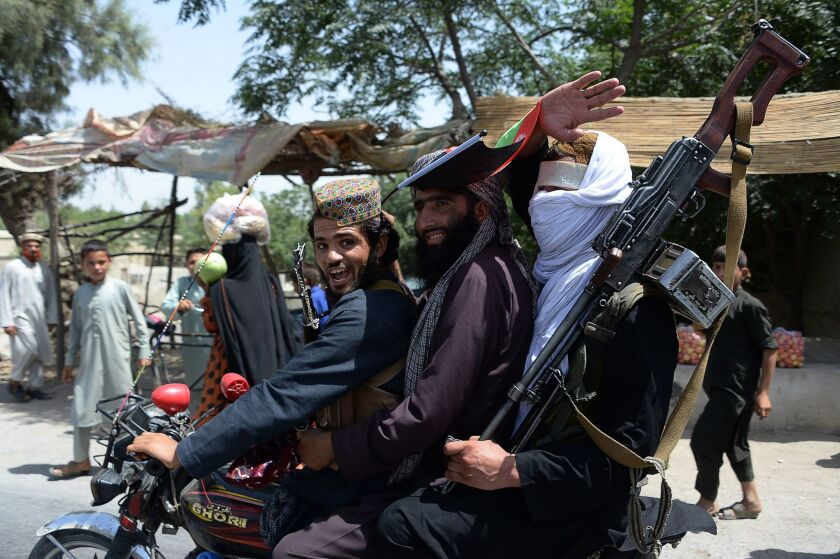 Taliban militants ride a motorbike as they celebrate a cease-fire on the second day of Eid in Jalalabad, Afghanistan, on June 16, 2018.