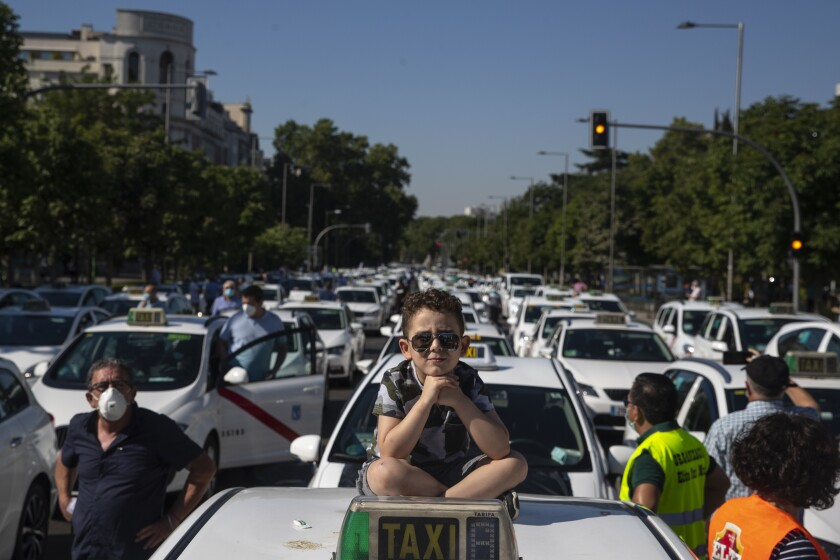 A child sits on the roof of a taxi during a taxi driver protest in downtown Madrid, Spain, Tuesday, June 30, 2020. Taxi drivers are demanding assistance due to lack of clients and private hire. (AP Photo/Manu Fernandez)