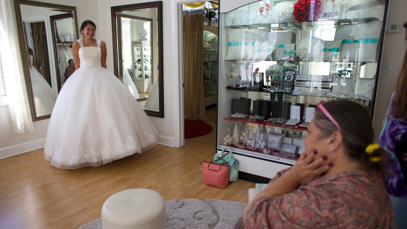 "Audrey Arellano, 14, of Irvine shows off a princess-style quinceañera dress at Genesis Bridal Boutique.""The newer clientele, the Americans and younger generation Hispanics are more selective. They don't want as many ruffles in their dresses,"" shop owner Lilia Cerpas says."