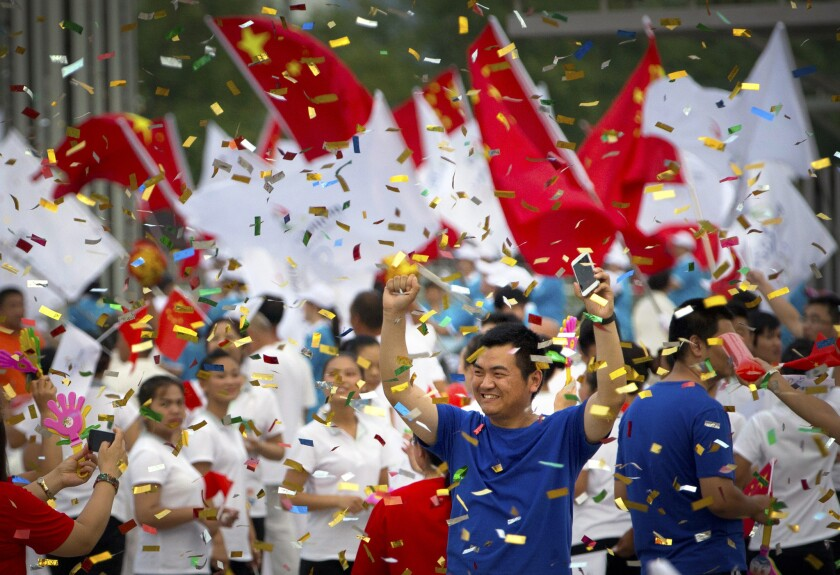 Chinese celebrate outside of the Beijing Olympic Stadium following an announcement Friday that Beijing will host the 2022 Winter Olympics.