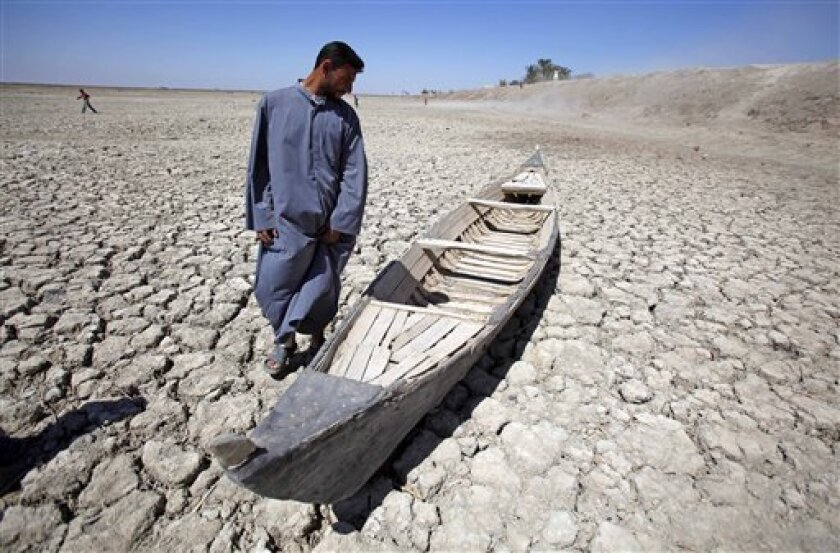 In this photo taken Friday, March 27, 2009, Akeed Abdullah stands next to his boat in a dried marsh in Hor al-Hammar in southern Iraq. A severe drought is threatening Iraq's southern marshes, the traditional site of the biblical Garden of Eden, just as the region was recovering from Saddam Hussein's draining of its lakes and swamps to punish a political rebellion. (AP Photo/Hadi Mizban)