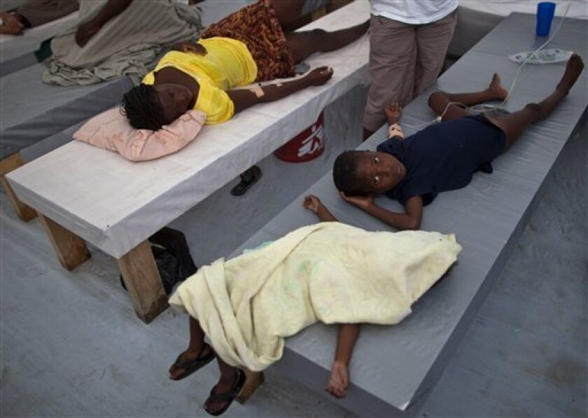 A sick boy lies next to the body of an unidentified three-year-old girl, who according to doctors, died a few minutes before of cholera at the St Catherine hospital in Cite Soleil, Port-au-Prince, Haiti, Wednesday, Nov. 10, 2010. Doctors and aid groups are rushing to set up cholera treatment centers across Haiti's capital as officials warn that the disease's encroachment into the city will bring a surge in cases. Cholera has killed more than 580 people across the country according to the Haiti's health ministry. (AP Photo/Ramon Espinosa)