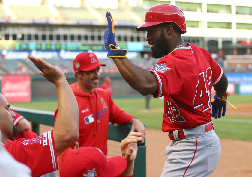 Angels' Brian Goodwin gets a high-five from teammate Albert Pujols.