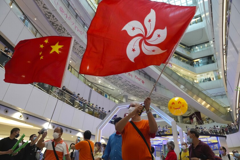 FILE-In this Friday, July 30, 2021, file photo, people wave a Hong Kong flag and a Chinese national flag as they watch Olympics events at a shopping mall in Hong Kong. Hong Kong police arrested a man Friday, July 30, 2021, on suspicion of insulting the national anthem, after he was allegedly caught booing the Chinese national anthem and waving a Hong Kong colonial flag while watching an Olympic event at a mall. (AP Photo/Vincent Yu, File)
