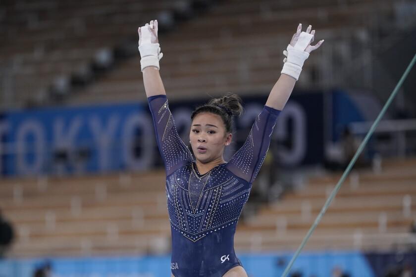 Suni Lee holds both arms high.