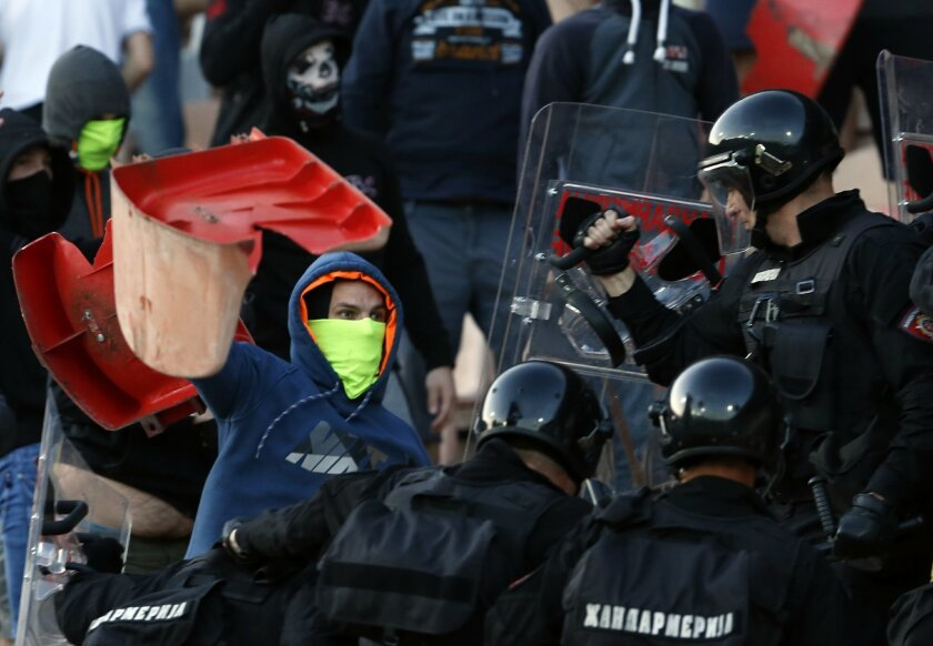 FILE - In this Saturday, April 16, 2016. file photo, Serbian riot police officers clash with Red Star soccer fans during a Serbian National soccer league derby match between Red Star and Partizan, in Belgrade, Serbia. Hooliganism is making a comeback, and the timing could be bad with four high-risk