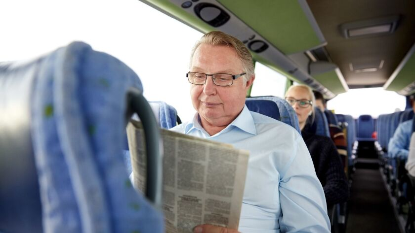 happy senior man reading newspaper in travel bus