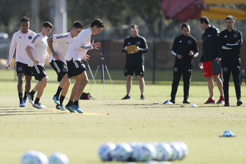 Inter Miami CF head coach Diego Alonso, right, watches players participate in drills during a team practice session in January.