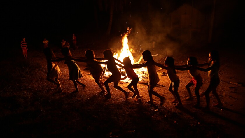 Tenetehara Indigenous children play around a campfire during a festival in the Alto Rio Guama Indigenous Reserve, where they have enforced six months of isolation during the new coronavirus pandemic, near the city of Paragominas, Brazil, Monday, Sept. 7, 2020. The Indigenous group, also known as Tembe, are celebrating and giving thanks that none of their members have fallen ill with COVID-19. (AP Photo/Eraldo Peres)