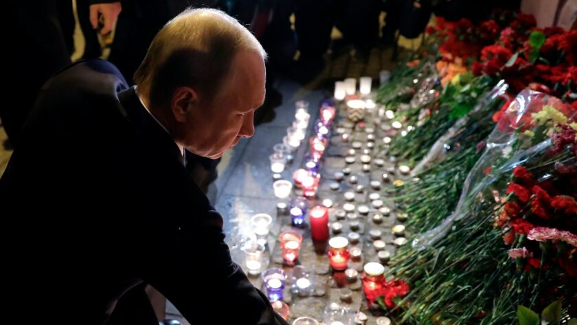 Russian President Vladimir Putin lays flowers after a bomb attack in St. Petersburg, Russia.