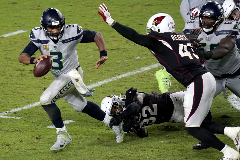 Seattle Seahawks quarterback Russell Wilson (3) escapes the reach of Arizona Cardinals strong safety Budda Baker (32) as outside linebacker Haason Reddick (43) pursues during the second half of an NFL football game, Sunday, Oct. 25, 2020, in Glendale, Ariz. (AP Photo/Ross D. Franklin)