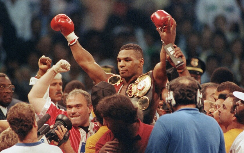 """Mike Tyson is lifted by the crowd upon winning his bout with challenger Carl """"The Truth"""" Williams"""