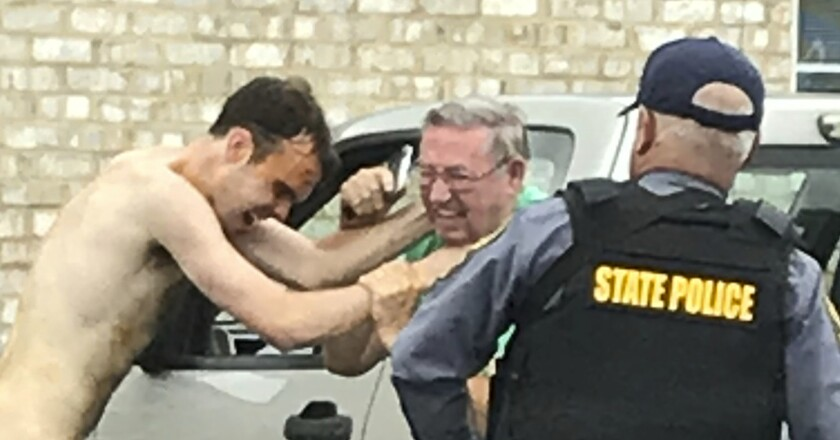 Matthew Bernard puts his hands on a man as a state police officer attempts to take him into custody Tuesday in Keeling, Va. The wife, toddler son and mother-in-law of minor league baseball player Blake Bivens have been killed. Bernard, Bivens' brother-in-law, has been charged with first-degree murder.