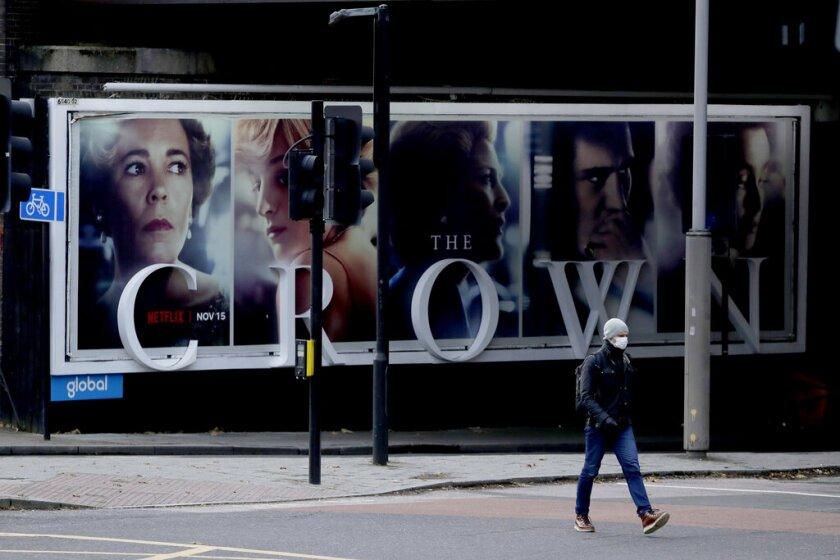 """ARCHIVO - un hombre pasa frente a un anuncio de la serie de Netflix """"The Crown"""" en Londres."""