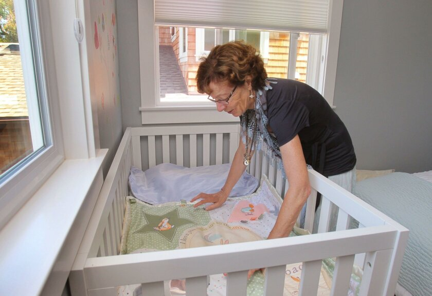 Susan Kurtik spreads out a blanket on the crib used for the foster children in her Encinitas home.