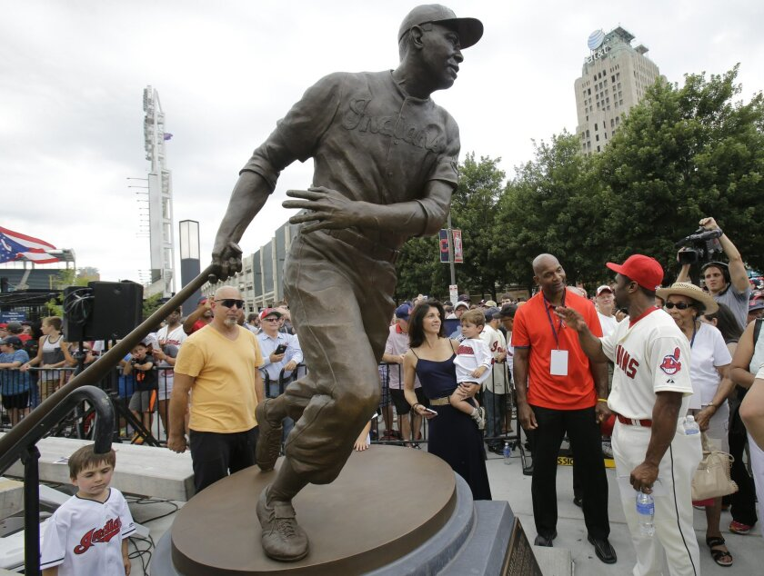 Larry Doby Jr., in red shirt, talks with Michael Bourn after the unveiling of a statue of Hall of Fame Larry Doby Saturday, July 25, 2015, in Cleveland. Doby broke the color barrier in the AL on July 5, 1947, just months after Jackie Robinson played for the Brooklyn Dodgers. Doby spent nine seasons with Cleveland and helped lead the Indians to a World Series title in 1948. He had a career .283 average with 253 homers. He led the league with 32 homers and 126 RBIs in 1954, when the Indians won 111 games. Before joining the Indians, Doby starred for Newark in the Negro League. He retired following the 1959 season. Doby's No. 14 was retired in 1994, 47 years after he was signed by Indians owner Bill Veeck. A seven-time All-Star, Doby died in 2003 at the age of 79. (AP Photo/Tony Dejak)