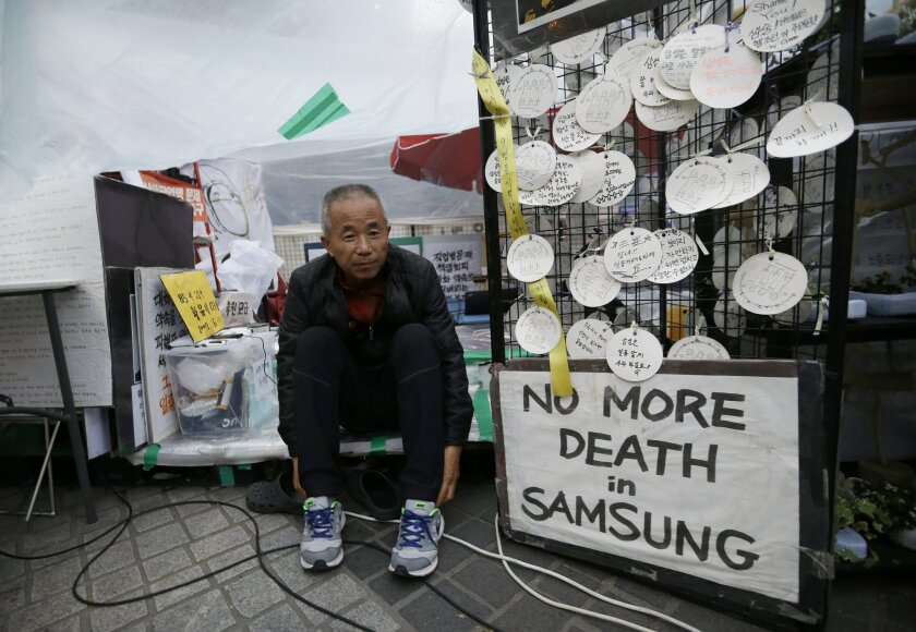 In this April 22, 2016 photo, Hwang Sang-gi, father of Hwang Yu-mi, a former Samsung factory worker who died of leukemia at the age of 22, wears shoes in order to an interview outside Samsung buildings in Seoul, South Korea. Yu-mi went to work bathing silicon wafers in chemicals at a Samsung factor