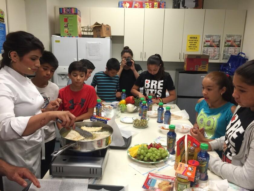 Chef Cindy Rueda aparece con sus ayudantes quienes son miembros del Variety Boys & Girls Club en Boyle Heights.