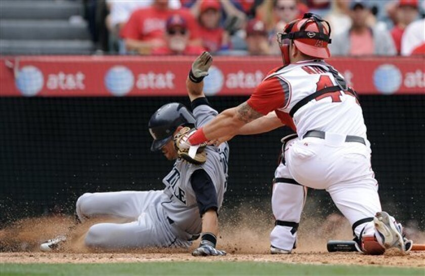 Seattle Mariners' Ichiro Suzuki, left, of Japan, is tagged out by Los Angeles Angels catcher Mike Napoli, right, while trying to score on a hit by teammate Adrian Beltre during the eighth inning of a baseball game, Sunday, May 31, 2009, in Anaheim, Calif. (AP Photo/Mark J. Terrill)