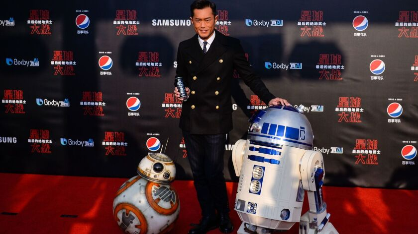 """Hong Kong actor and film producer Louis Koo poses with droids BB-8, left, and R2-D2 on the red carpet for the Chinese premiere of """"Star Wars: The Last Jedi"""" at the Shanghai Disney Resort on Dec. 20, 2017."""