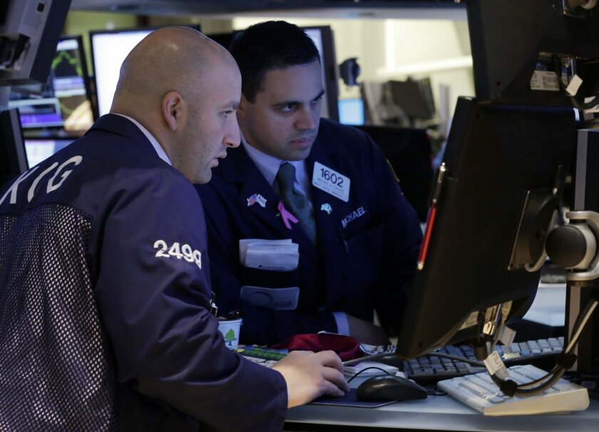 In this Tuesday, Dec. 3, 2013,photo, specialists Joe Parisi, left, and Michael Cacace work at a post on the floor of the New York Stock Exchange. World stock markets were in the red Thursday Dec. 5, 2013 after strong U.S. economic data renewed fears that the Federal Reserve may start cutting its monetary stimulus this month. (AP Photo/Richard Drew)