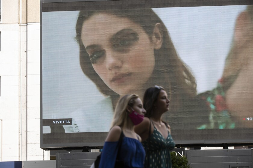 Pedestrians pass by a screen showing a Vivetta model during the Milan Digital Fashion Week, in Milan, Italy, Tuesday, July 14, 2020. Forty fashion houses are presenting previews of menswear looks for next spring and summer and pre-collections for women in digital formats, due to concerns generated by the COVID-19. (AP Photo/Luca Bruno)