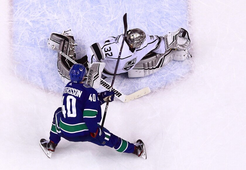 Kings goaltender Jonathan Quick makes a glove save off the shot by Vancouver's Elias Pettersson.